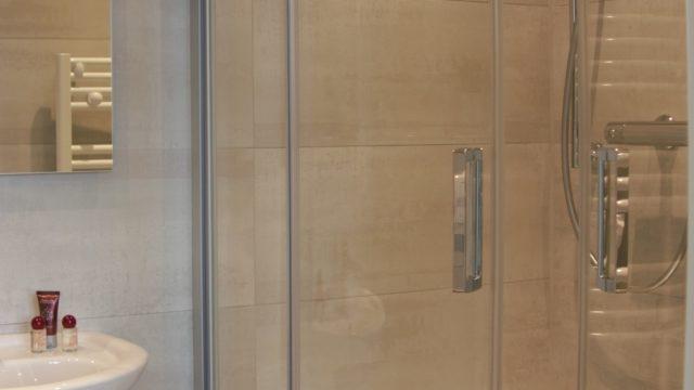 Ein kleines Duschbadezimmer mit Feinsteinzeug Fliesen an Wand & Boden ohne Kompromisse.